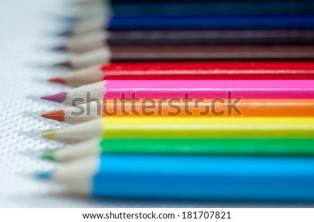 Row of colorful wooden crayons, macro with extremely shallow dof. Selective focus. - stock photo