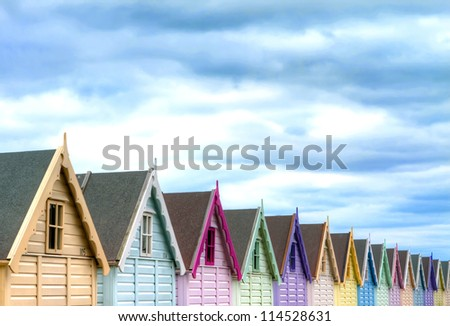 row of coloured beach huts on a gloomy day - stock photo