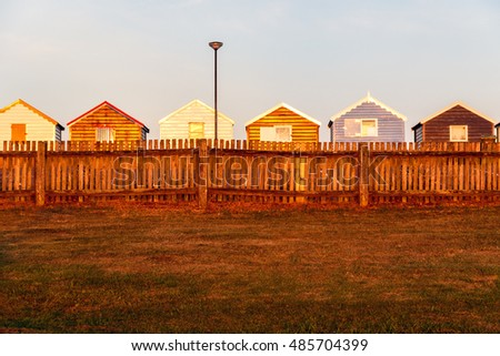 Row of colourful beach huts at sunset in Southwold, Suffolk, UK