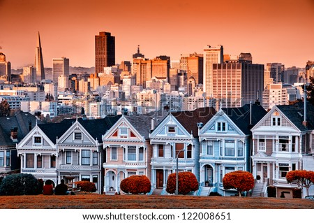 Row of colourful Victorian homes on Steiner Street with the San Francisco skyline behind. - stock photo