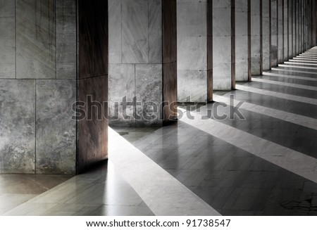 Row of columns with sunlight in the gaps and reflected in shiny floor