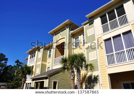 Row of condos with palm tree in front - stock photo