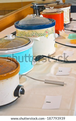 row of crock pots for chili cook-off in a restaurant - stock photo