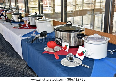 row of crock pots in a restaurant for chili cook off