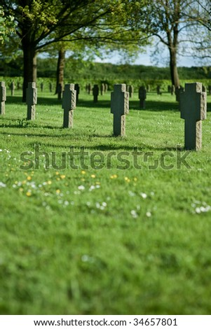 Row of crosses in cemetery during sunset, shallow DOF - stock photo
