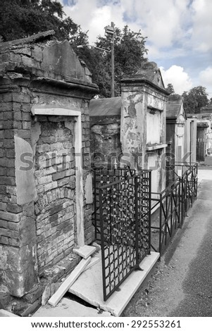 Row of crumbling brick tombs in New Orleans with black & white filter effect