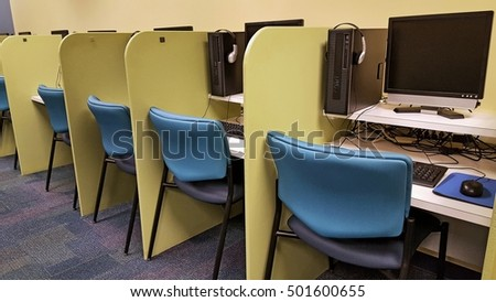 row of cubicles with computers in school classroom