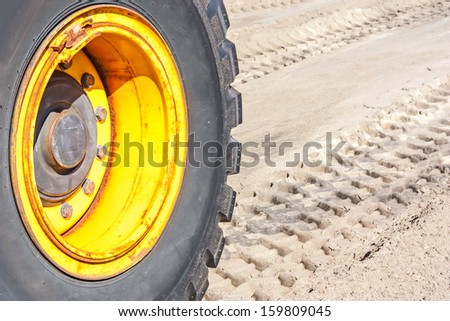 Row of deep tractor tire prints in the sand. Close up of industrial vehicle heavy black rubber tire, bright yellow metal wheel. Horizontal photo. - stock photo