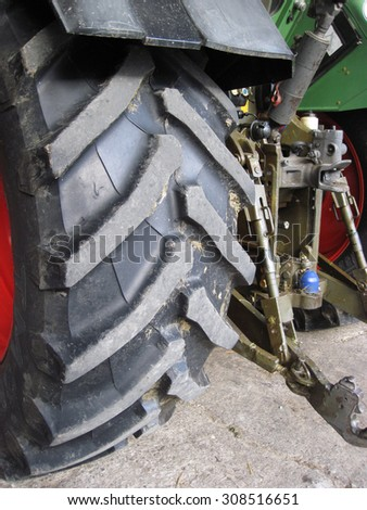 Row of deep tractor tire prints in the sand. Close up of industrial vehicle heavy black rubber tire, bright red metal wheel. - stock photo