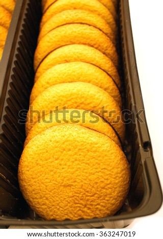 Row of delicious chocolate sponge biscuit chip cookies with jelly in brown box - stock photo