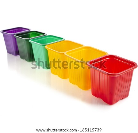 Row of disposable colorful plastic flowerpot isolated on white background  - stock photo