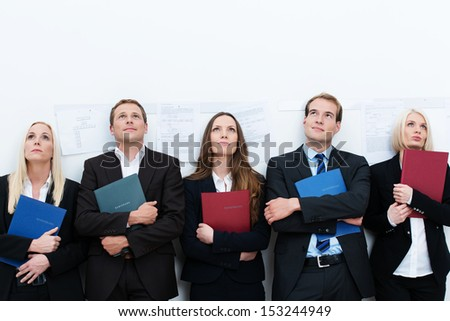 Row of diverse professional applicants waiting to be called into an interview for a vacant corporate job - stock photo