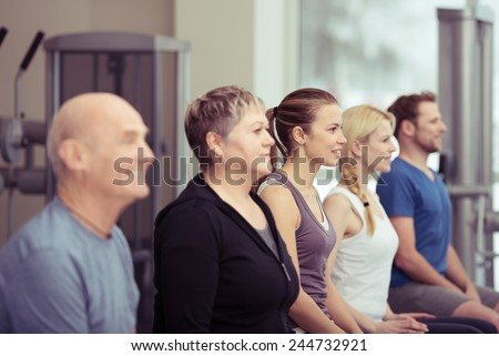 Row of diverse young and old people in a gym sitting listening to the instructor with focus to an elderly lady in the centre in a healthy lifestyle concept