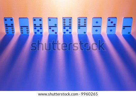 Row of dominos with light casting long shadows. - stock photo