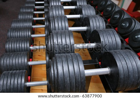 row of dumbell weights in gym room. for lifting or fitness.  - stock photo