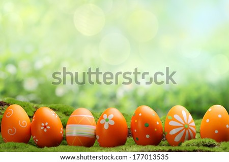 Row of easter eggs on meadow - stock photo