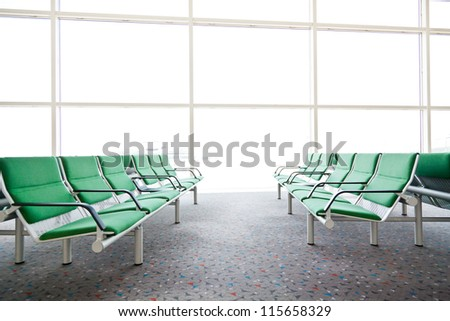 Row of empty green seats in airport - stock photo