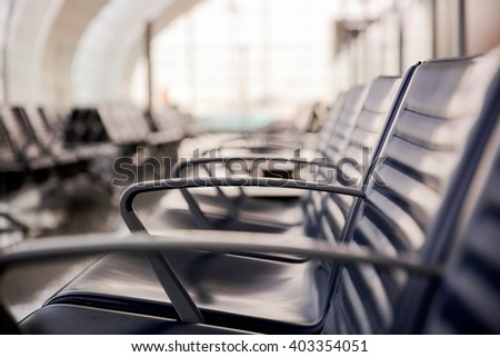 Row of  empty leather chairs in the departure lounge at the airport.  International airport terminal and the window background.  - stock photo