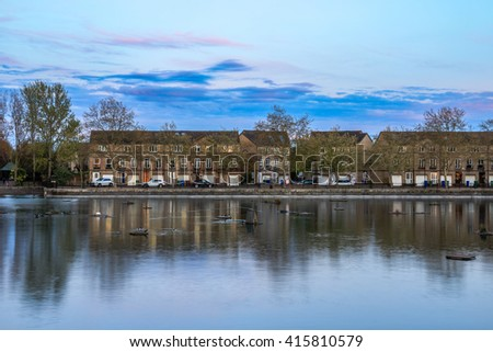 Row of English terraced houses on the waterfront at Surrey Water, Bermondsey, London with sunset skyline and floating bird nesting pontoons