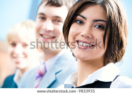 Row of faces of successful professionals with woman in front - stock photo