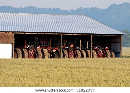 Row of farming tractors parked side by side in a shed.  Viewed across a field of young wheat crops.  An early morning haze clouds the trees and sky in the distance. - stock photo