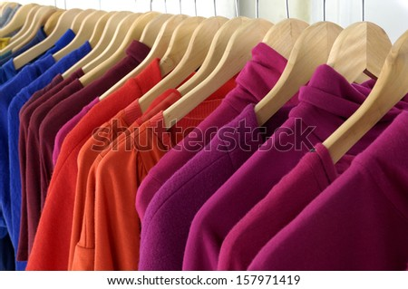 Row of female colorful clothes on Hangers - stock photo