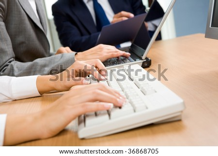 Row of female?s hands touching keys of laptop on background of businessman