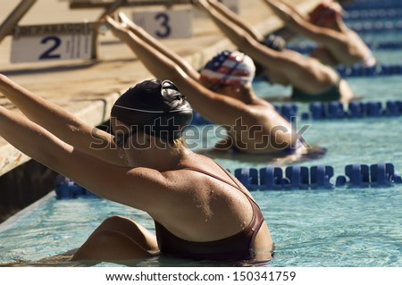 Row of female swimmers holding onto starting block preparing to swim backstroke - stock photo