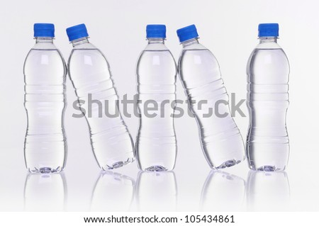 row of five water bottles with reflection