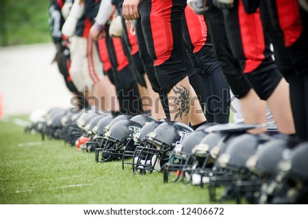 Row of football helmets and feet on grass, selective focus - stock photo