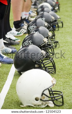 Row of football helmets on grass, focus on second one - stock photo