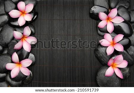 Row of frangipani with zen stones on mat - stock photo