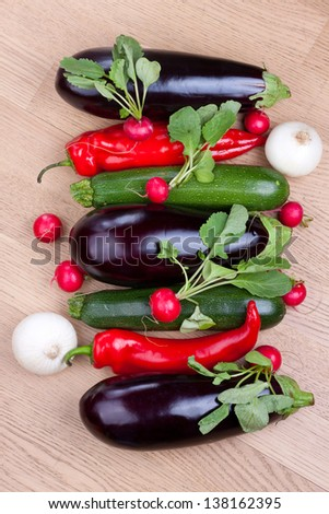 Row of fresh colorful vegetables on wooden background shot from above - stock photo