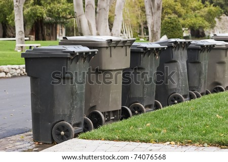 Row of garbage bins are ready to be collected on a residential street. - stock photo