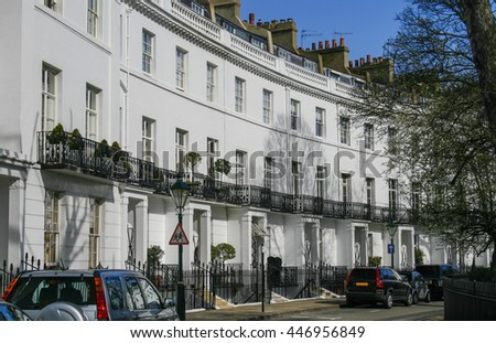 Row of Georgian terraced houses in London with parked cars in front - stock photo