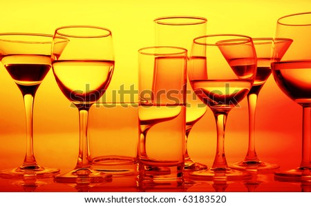 row of glass glasses with refractions and reflections on an equal surface in yellow orange warm lighting - stock photo
