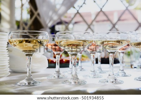 Row of glasses filled with champagne are lined up ready to be served.