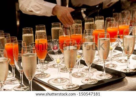 Row of glasses filled with champagne lined up ready to be served  - stock photo