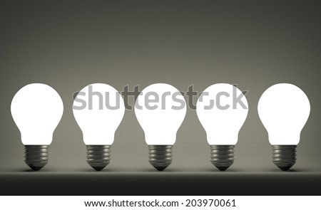 Row of glowing tungsten light bulbs on gray textured background - stock photo