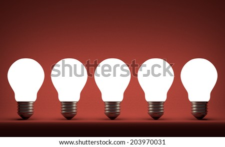 Row of glowing tungsten light bulbs on red textured background - stock photo