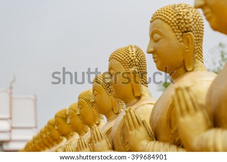 Row of golden Buddha statue among many small Buddha statues in countryside public temple named MAKHA BUCHA BUDDHIST MEMORIAL PARK in Nakornnayouk, Thailand - stock photo