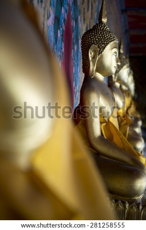 Row of golden seated buddhas close up in a Buddhist temple in Bangkok Thailand