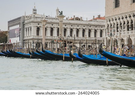 Row of gondolas near Doges palace in summer Venice, St. Marco lion statue in summer Venice - stock photo