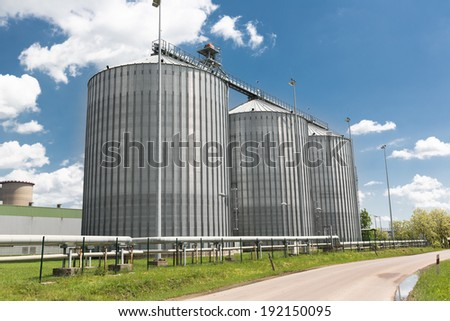 row of grain silos set in an agricultural processing plant - stock photo