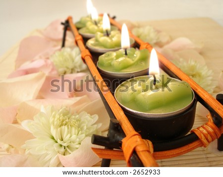 row of green candles over  straw matt with rose petals - stock photo