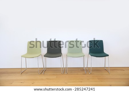 Row of 4 green chairs set against white wall in waiting area