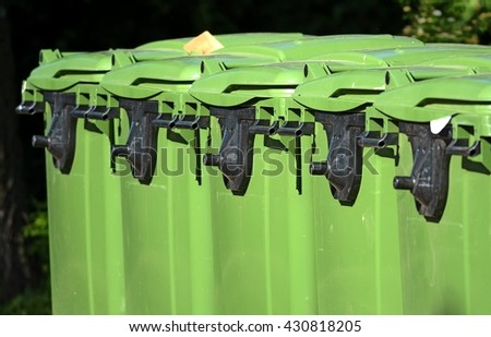 row of green large plastic trash cans on wheels with black handles landscape crop close up - stock photo