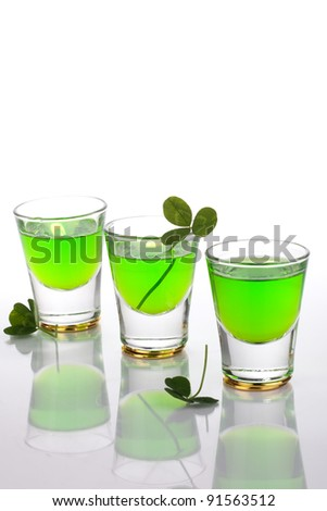 Row of green liquor shots for St Patrick's Day and clover leafs. - stock photo