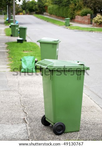 Row of green recycling bins in urban street