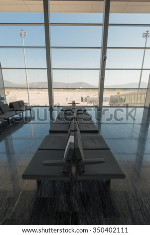 Row of grey chairs at airport with big windows and blue sky - stock photo